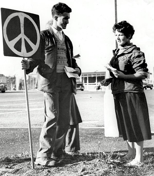 1950s peace activists holding a placard displaying the CND logo