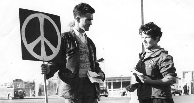 1950s peace activists holding a placard displaying the CND symbol